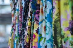 Färgrika tyger som hänger och fodras Tyger med olika modeller och kulöra rader arkivbilder