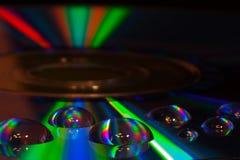 Färgrika vattendroppar på CD-/DVDdiskett royaltyfria bilder