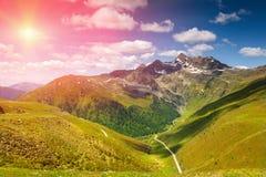 Färgrikt alpint landskap med solen som ner ställer in Arkivbild