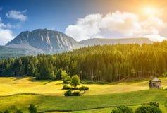 Färgrikt alpint landskap med solen som ner ställer in Fotografering för Bildbyråer