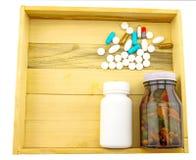 Färgrikt av preventivpiller- och flaskmedicin i den wood asken Royaltyfria Foton