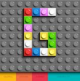 Färgrikt bokstavsG från byggnadslegotegelstenar på grå legobakgrund Lego bokstav M Arkivbild
