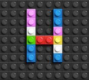 Färgrikt bokstavsH från byggnadslegotegelstenar på svart legobakgrund Lego bokstav M Arkivfoto