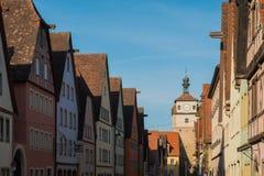 Färgrikt byggnads- och klockatorn i gammal gata av Rothenburg ob Royaltyfria Foton