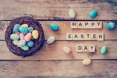 Färgrikt easter ägg i redet och trätext av den lyckliga påsken Arkivbilder