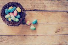 Färgrikt easter ägg i redet på wood bakgrund med utrymme Royaltyfria Foton