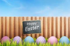 Färgrikt easter ägg med den lyckliga easter hälsningen på svart teckenboa Arkivfoto