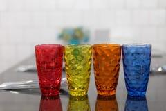 färgrikt exponeringsglas, sked, gaffel på tabellen i restaurang Arkivbild