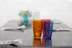färgrikt exponeringsglas, sked, gaffel på tabellen i restaurang Arkivfoto