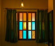Färgrikt fönster med gardinen på det mörka huset arkivfoton