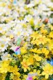 Färgrikt fejka fågeln på gula konstgjorda blommor Royaltyfri Foto