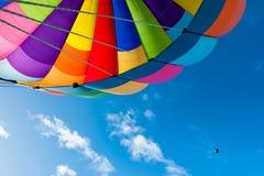Färgrikt flyg för ballong för varm luft i den blåa himlen Royaltyfri Foto