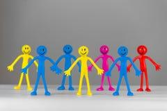 Färgrikt folk på grå bakgrund Arkivfoton