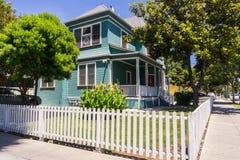 Färgrikt hus på ett gatahörn som omges av ett vitt staket Arkivbild