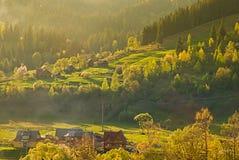 Färgrikt landskap med byn och berg Arkivbilder