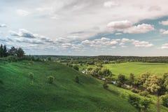 F?rgrikt ljust Sunny Green Field River Summer landskap med bl?a molnig himmel, tr?d och kullar royaltyfri fotografi