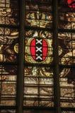 Färgrikt målat glassfönster inom den gotiska gamla kyrkan med vapenskölden av Amsterdam Fotografering för Bildbyråer