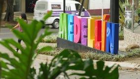 Färgrikt Medellin tecken på gatan med gröna sidor, trafik och att gå för flicka arkivfilmer