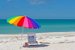 Färgrikt paraply och stol på stranden Royaltyfria Foton