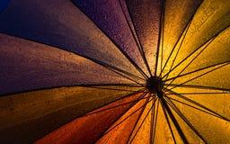 Färgrikt paraply under hällregn Arkivbilder