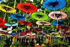 Färgrikt regnbågepappersparaply som hänger i himlen arkivbild