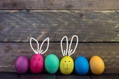 Färgrikt roligt easter ägg på trätabellen lyckliga easter Royaltyfri Fotografi