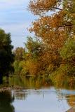 Färgrikt sceniskt idylliskt höstlandskap på en flodkust med träd som reflekterar på vattnet på en solig höstdag Arkivbild