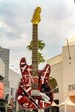 Färgrikt stadsgatatecken av en röd elektrisk gitarr arkivfoto