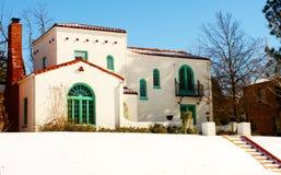 Färgrikt sydvästligt hus på kullen i snön med moment som upp till leder den Arkivbild