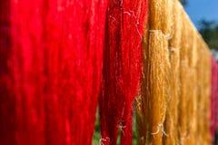 Färgrikt tyg som hänger för att torka efter traditionella färgprocesss i Luang Prabang, Laos royaltyfri fotografi