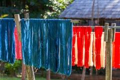 Färgrikt tyg som hänger för att torka efter traditionella färgprocesss i Luang Prabang, Laos arkivbild