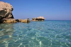 Färgrikt vatten av den Konnos fjärden i Cypern med vaggar och stenar Arkivfoto