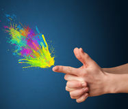 färgstänk är kommande ut ur vapnet formade händer Arkivfoto