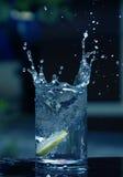 Färgstänk av blått vatten genom att använda limefruktskivan Royaltyfri Fotografi