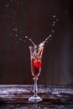 Färgstänk av Champagne och jordgubbar in i ett exponeringsglas Royaltyfri Foto