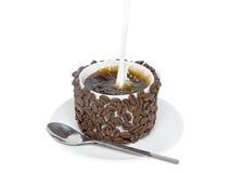 Färgstänk av hällt in mjölkar i en kopp med kaffe. Arkivfoton