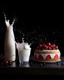 Färgstänk av mjölkar i ett exponeringsglas och en krus och en ljusbrun kaka med jordgubbar på en svart bakgrund Djupfryst rörelse Arkivfoton
