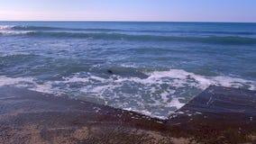 Färgstänk av vatten från de stormiga vågorna som bryter på vågbrytaren på strand Blått gör klar himmel stock video