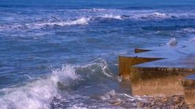 Färgstänk av vatten från de stormiga vågorna som bryter på vågbrytaren på strand Slapp fokus arkivfilmer