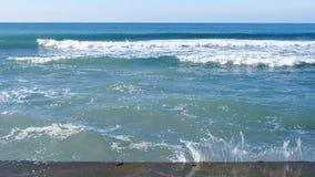 Färgstänk av vatten från de stormiga vågorna som bryter på vågbrytaren på strand, stormhav med vågor som kraschar mot stock video