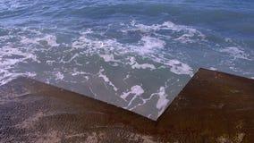 Färgstänk av vatten från de stormiga vågorna som bryter på vågbrytaren på strand Top beskådar stock video