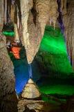 Färgstänk av vatten från en stalaktit som skapar en stalagmit under den i en grotta arkivbilder