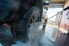 Färgstänk av vatten med tvål flyger i olika riktningar från en ström av ett högtryck Biltvätten för manwasheshand med vatten Royaltyfria Bilder