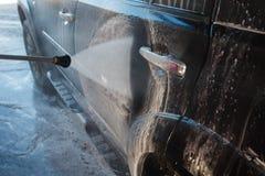 Färgstänk av vatten med tvål flyger i olika riktningar från en ström av ett högtryck Biltvätten för manwasheshand med vatten Royaltyfri Bild