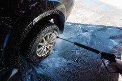 Färgstänk av vatten med tvål flyger i olika riktningar från en ström av ett högtryck Biltvätten för manwasheshand med vatten Royaltyfria Foton