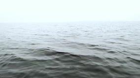 Färgstänk av vatten på sidan av ett snabbt rörande fartyg på havet på en molnig dag lager videofilmer