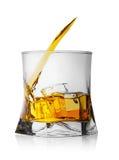 Färgstänk av whisky med is i exponeringsglas Royaltyfria Bilder