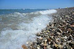 Färgstänk för havsvatten på den steniga stranden royaltyfria bilder