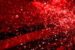Färgstänk för rött vatten på den svarta bakgrunden Royaltyfria Foton