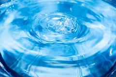 Färgstänk från en droppe av vatten Regndroppar på en blå bakgrund Texturen av vattnet Aqua krusning, turkos, makro arkivfoton